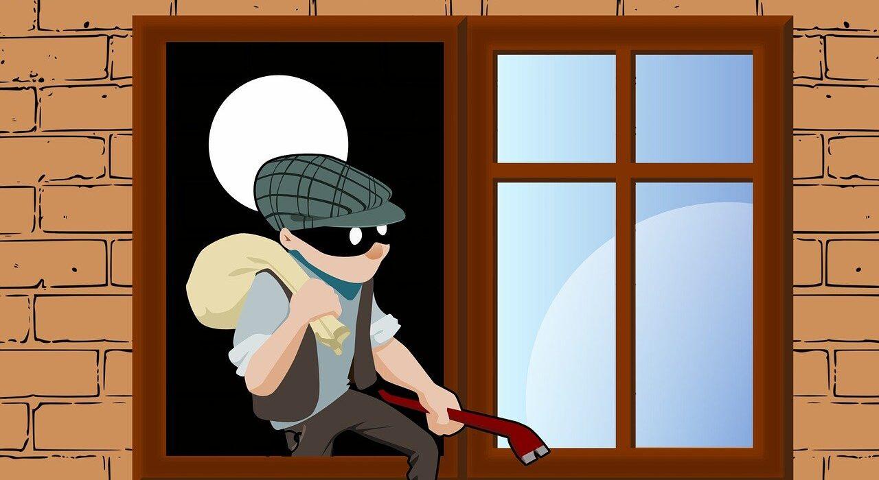 un cambrioleur qui passe par la fenêtre